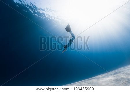 Woman freediver glides over sandy bottom in a tropical clear sea with sun rays