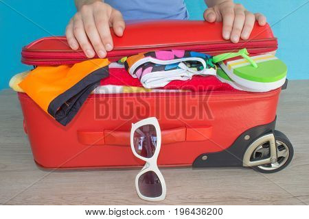 Woman hands packing her red suitcase. Travel and vacations concept. Open traveler's bag with clothing accessories