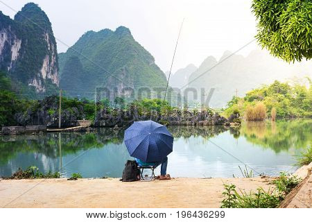 Lonely Fisherman In A Scenic Lake Of Guangxi Province, China