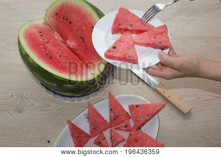 Slices of juicy and tasty watermelon on a white plate. Triangle shaped watermelon slices