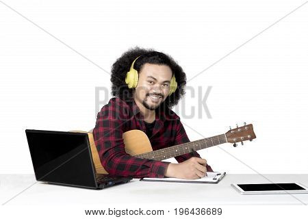 Image of an afro musician holding a guitar while composing a song in the studio isolated on white background
