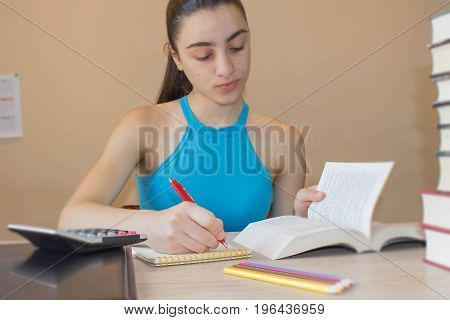 Student Young Girl working on his homework. Portrait of pretty girl high school student studying and writing