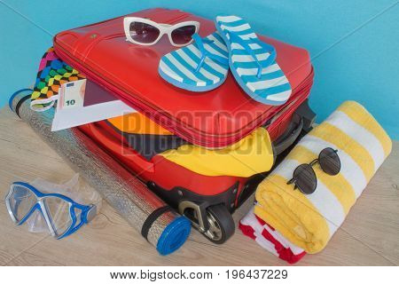 clothes and accessories in red suitcase things prepared for travel. red suitcase with clothing on table