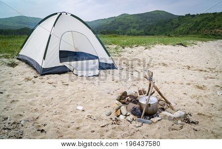 tent and campfire on the sandy shore
