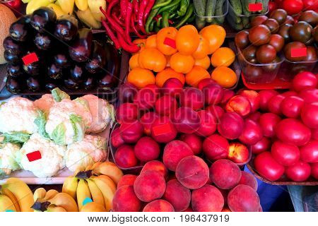 Fresh ripe vegetables and fruits on the counter in the market. Close-up.