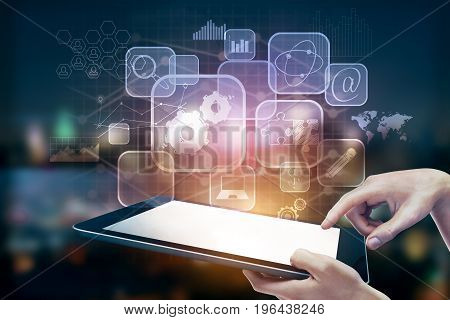 Hands using tablet with digital business icons on blurry night city background. Technology and innovation concept. Double exposure