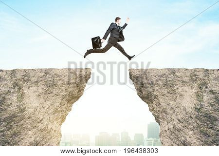 Side view of businessman jumping from cliff to cliff on bright city background. Risk concept