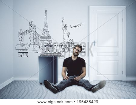 Front view of european guy sitting on floor of concrete room interior with suitcase. Business trip concept. 3D Rendering