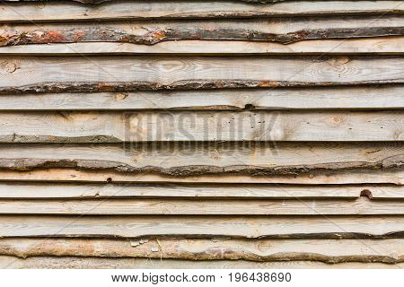 Construction site. Fence from a rough pine board with bark. Ukraine the Kiev area