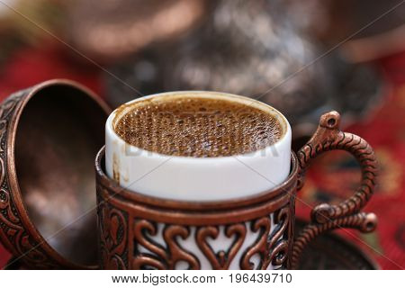Close up of Turkish coffee served in a traditional metal dish cap.