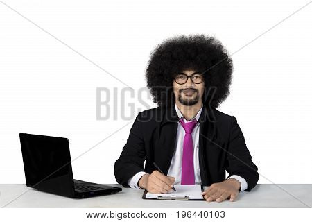 Portrait of Afro businessman wearing formal suit while writing and smiling at the camera isolated on white background
