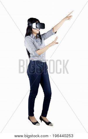 Portrait of young businesswoman using a virtual reality goggles while standing in the studio