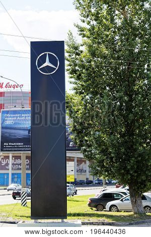 Ulyanovsk Russia - July 22 2017: Promotional stand with Mercedes signs near building of selling and service center which provides vehicle maintenance repairs and diagnostics.