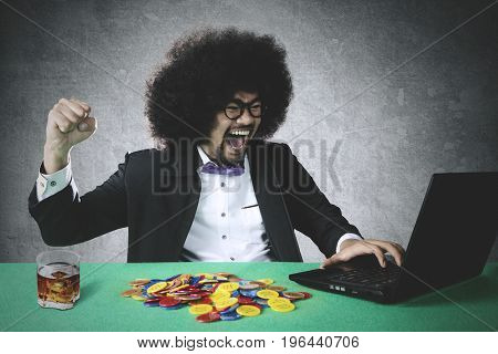 Portrait of cheerful gambler winning online poker with many chip and laptop on the table