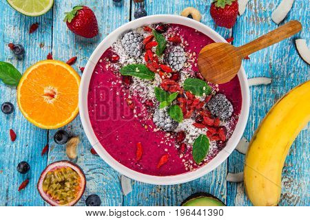 Smoothie bowl with fresh berries, nuts, seeds, fruit and vegetables. Healthy breakfast.
