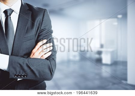 Businessman with folded amrs standing in blurry office interior. Copy space. Executive concept. 3D Rendering