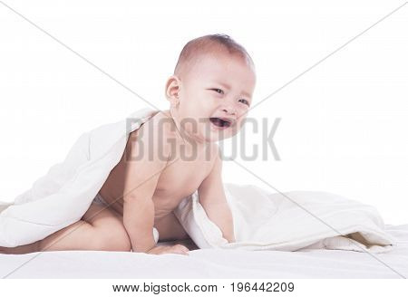 Picture of cute baby looks sad while playing on the bed isolated on white background