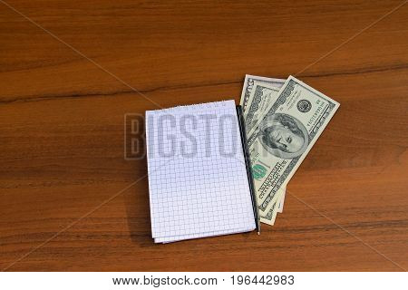 Notepad With Pen And Dollar Cash On Wooden Desk