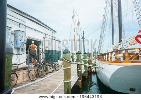 Key West , Florida, USA - June 26, 2012; Man standing bare backed in doorway of wharf shed with walkway and large sailing vessel moored alongside.