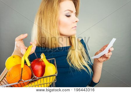 Worried woman holding shopping basket with fruits looking at bill receipt being scared of huge prices