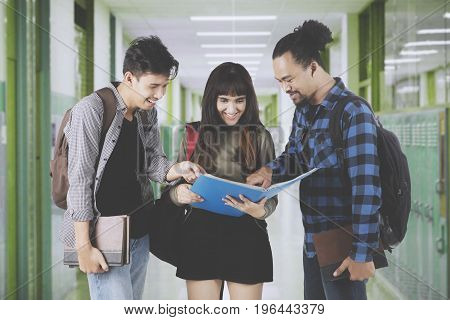 Three diversity students discussing an assignment while standing on the campus corridor