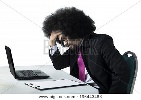 Portrait of a dizzy young Afro businessman working with a laptop computer on the table isolated on white background