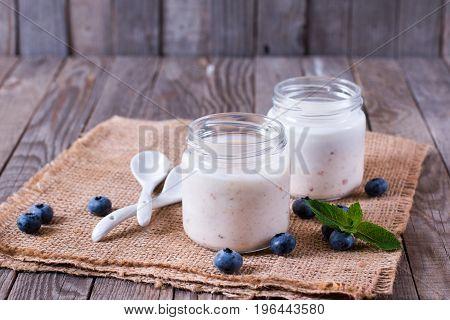 Fresh homemade yogurt in small jars served with berries