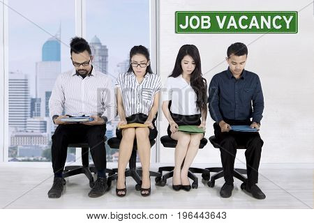 Group of strained multiethnic employee candidates waiting for interview in job vacancy recruitment