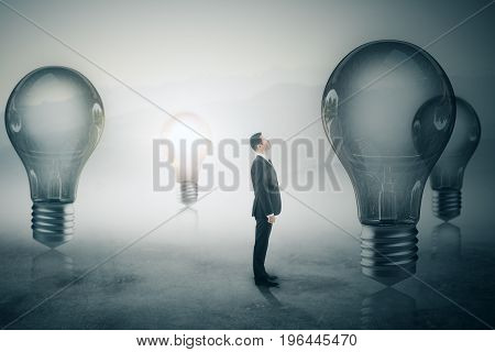 Side view of young adult businessman looking at glowing lamps on foggy gray background. Success and solution concept. 3D Rendering