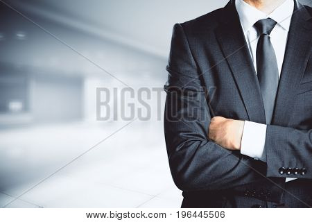 Businessman with folded amrs standing in blurry office interior. Copy space.Worker concept. 3D Rendering