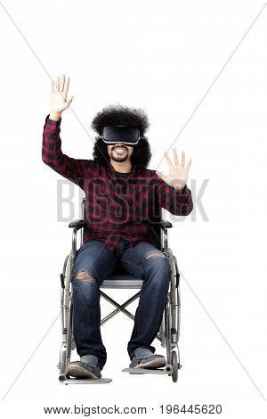 Handicapped Afro man wearing Virtual Reality glasses while touching something isolated on white background