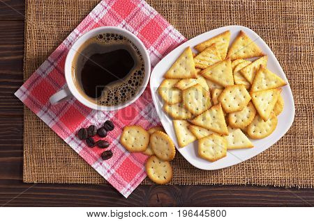 Crackers with cheese flavor and cup of coffee on wooden table top view