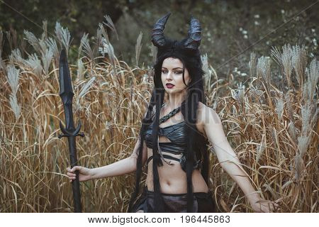 Portrait of a girl with horns stands in the thickets