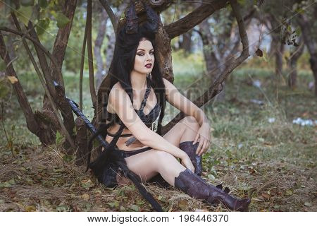 Woman from the tribe sits under a tree
