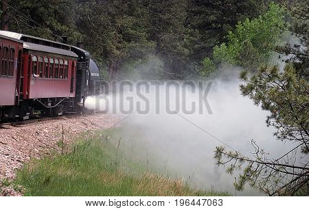 red vintage steam train spewing steam mountain