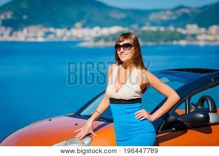 Beautiful Young Woman With Long Hair Standing Near Orange Cabriolet At The Mediterranean Sea Coast