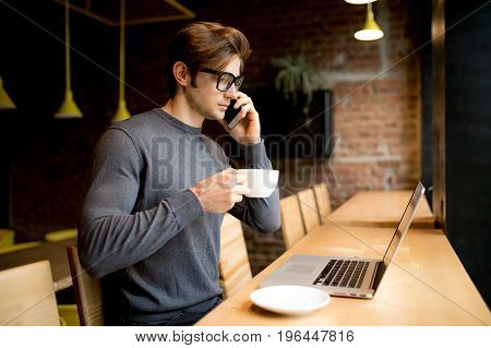 Young Man Speak Phone And Drink Coffee While Work At Laptop In Freelance In Coffee Shop