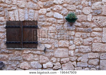 Decorative antique windows and an old wall with colorful plants in pots.