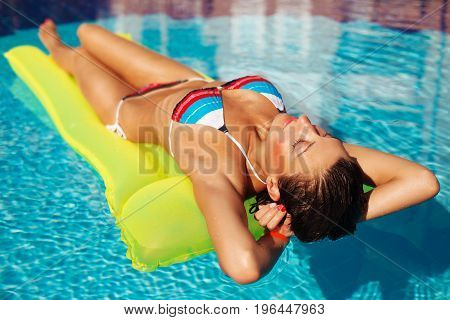 Portrait Of Beatiful Tanned Woman Relaxing In Swimming Pool In Cstriped Swimwear. Creative Gel Polis