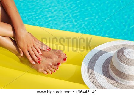 Portrait Of Beautiful Tanned Woman Relaxing In Swimming Pool Spa. Legs And Hands Close Up. Creative