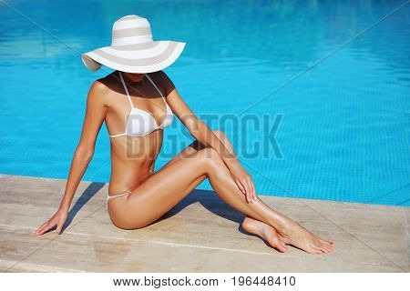 Portrait Of Beautiful Tanned Sporty Slim Woman Relaxing In Swimming Pool Spa. Creative White Hat And