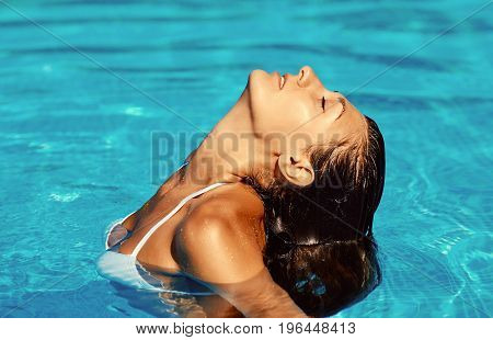 Portrait Of Beautiful Tanned Woman Relaxing In Swimming Pool Spa. Hot Summer Day And Bright Sunny Li