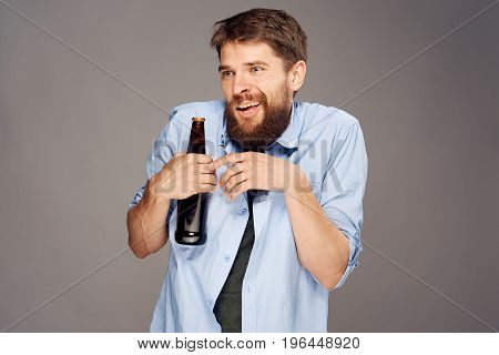 A young guy with a beard on a gray background holds a bottle of beer.