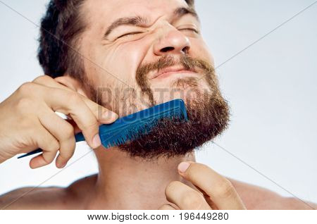 Young guy with a beard on a white isolated background combing out.
