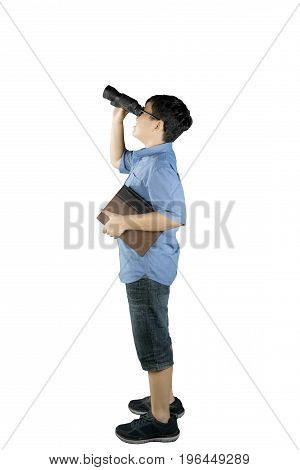 Portrait of schoolboy looking at something with a binocular while holding a book and standing in the studio