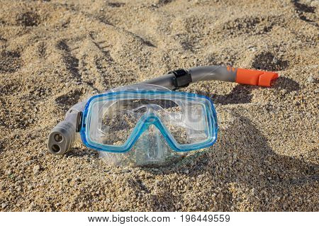 Snorkel mask with a tube on the sand in the rays of sunset, close up