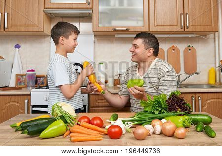 Father and son having fun with vegetables in home kitchen interior. Man and child. Fruits and vegetables. Healthy food concept
