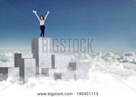 Successful businesswoman standing on high concrete wall while raising hands and holding megaphone