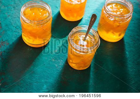 Four jars of pineapple jam on a turquoise table horizontal