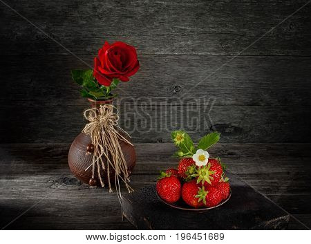 Ripe fresh strawberries in a clay pot in a rustic style. Art. Copy space. The horizontal frame.